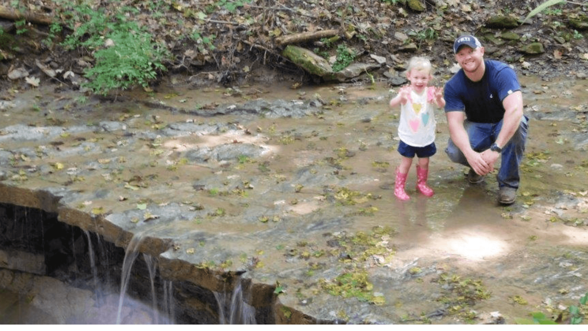 A family enjoying a waterfall on a hike - around the neighborhood Rivers Pointe Estates in Hebron, Kentucky